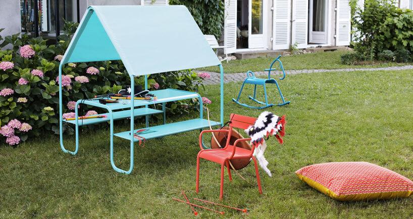 zestaw do zabawy dla dzieci zniebieskim stolikiem zławkami idachem oraz małe czerwone krzesełko wogrodzie