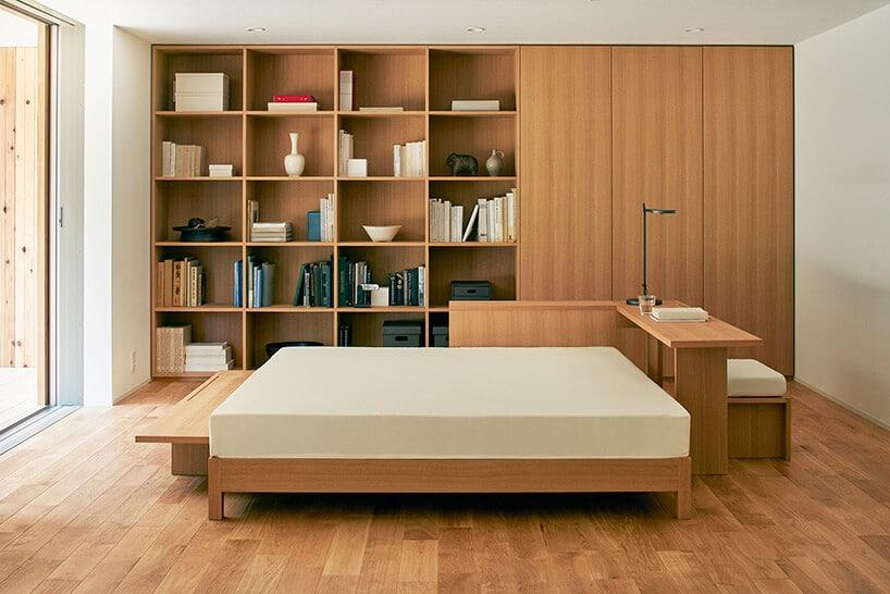 wnętrze sypialni zdużą ilością jasnego drewna oraz białym materacem oraz książkami wróżnych kolorach na regale