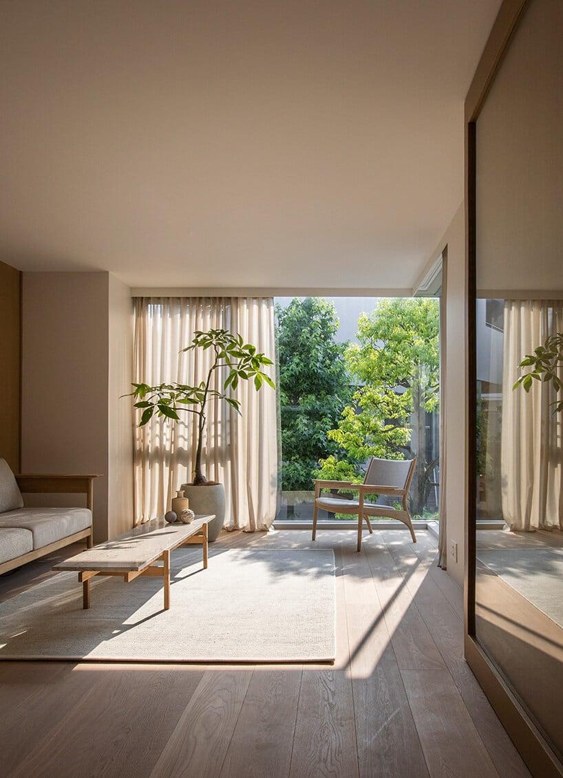 wnętrze wstylu japońskim zwysokim drzewkiem oraz lekkim fotelem wkolorze jasnej szarości
