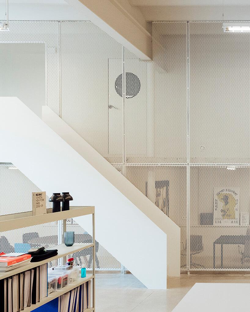 wnętrze zpełną białą balustradą schodową przy oddzielonej strefie zpaneli zdziurkowanym metalem wkolorze białym