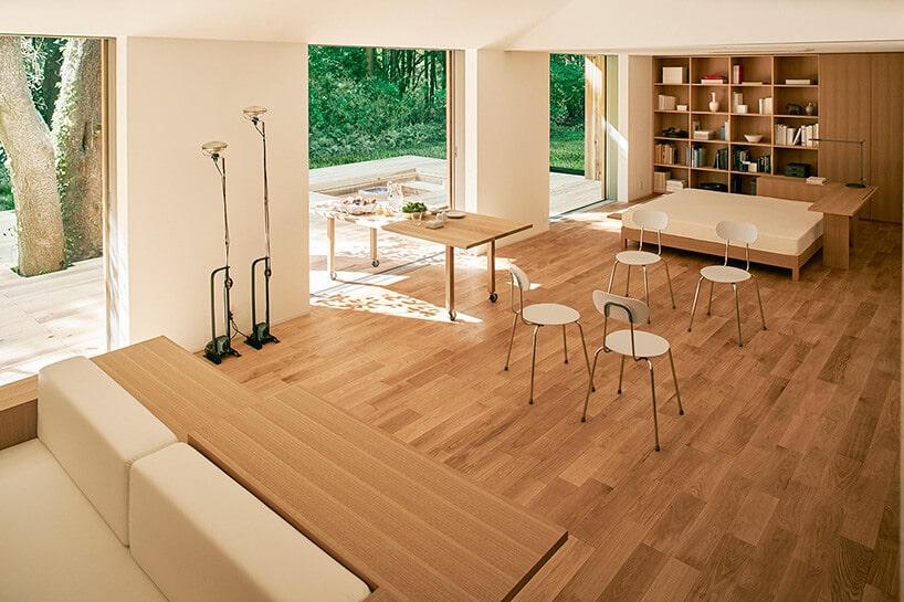 duży salon wykończony jasnym drewnem zprzeszkleniami oraz stołem na kółkach