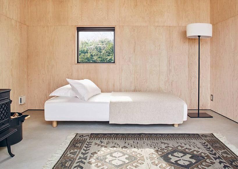 jasno betonowa podłoga zdywanem ze starymi wzorami oraz łóżkiem przy ścianie