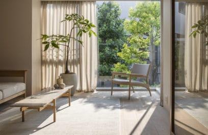 wnętrze w stylu japońskim z wysokim drzewkiem oraz lekkim fotelem w kolorze jasnej szarości