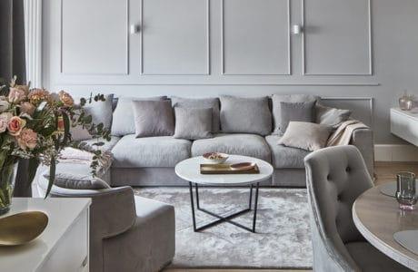 szare wnętrze z puszystą kanapą oraz poduszkami i ścianą ze sztukaterią w kolorze szarym