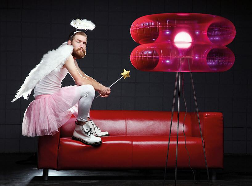mężczyzna przebrany za wróżkę siedzący na czerwonej sofie