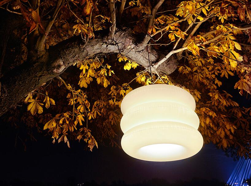 pufowa lampa wisząca na drzewie nocą