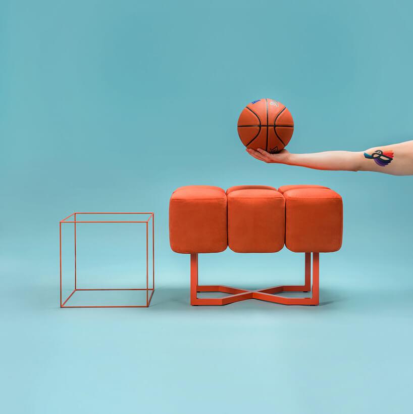 pomarańczowa pufa obok pomarańczowego stolika zprętów metalowych na niebieskim tle