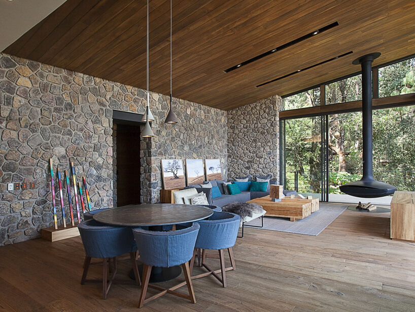 przestronny salon na ranczu zdrewnianą podłoga isufitem oraz kamienną ścianą