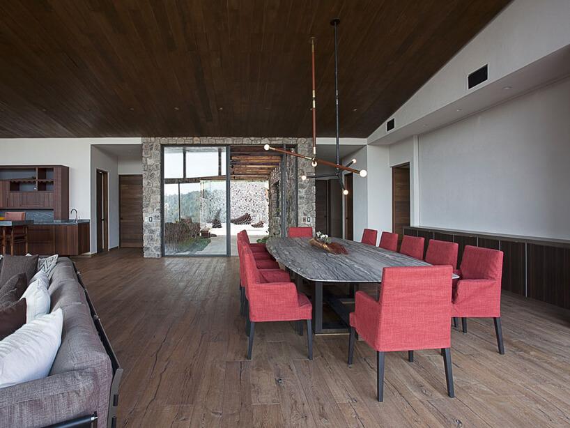 przestronna jadalnia zdużym stołem iczerwonymi krzesłami