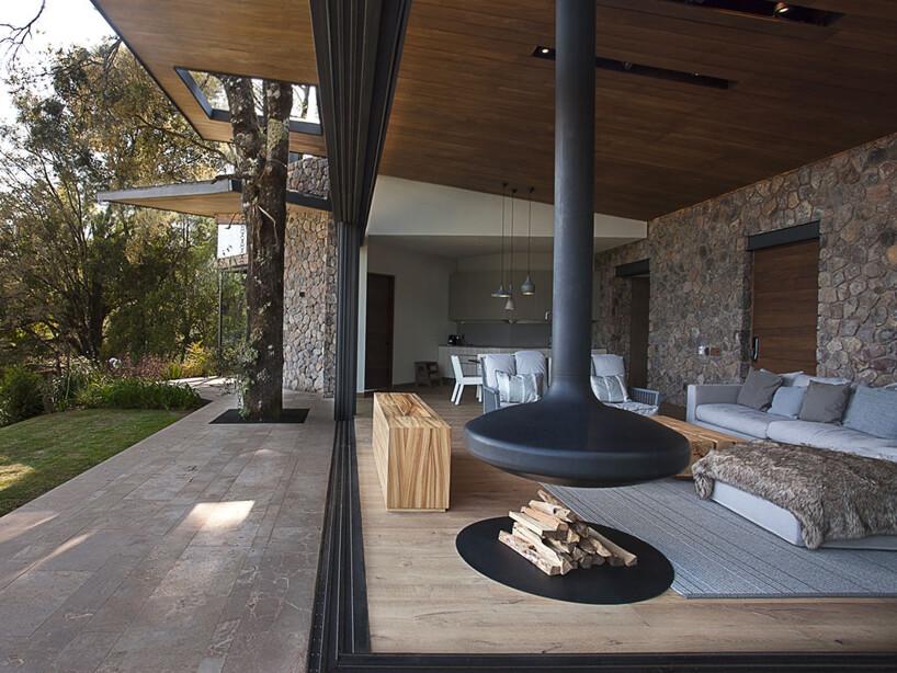 otwarty salon zwysokim czarnym paleniskiem zwidokiem na ogród