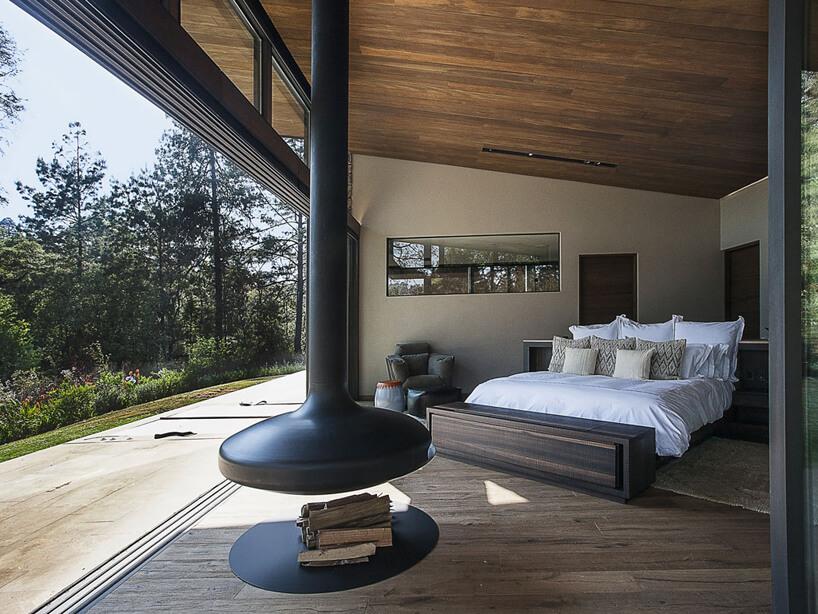 duża sypialnia zdużym łóżkiem nietypowym paleniskiem oraz rozsuwaną ściną