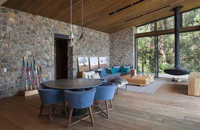 duży salon na ranczu z drewnianą podłoga i sufitem oraz kamienną ścianą