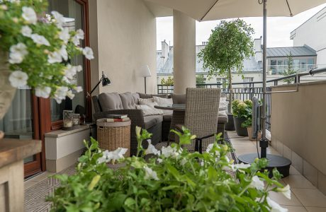 aranżacja większego balkonu w bloku z dużym narożnym siedziskiem przy słupie obok stołu i osłonięte dużym parasolem