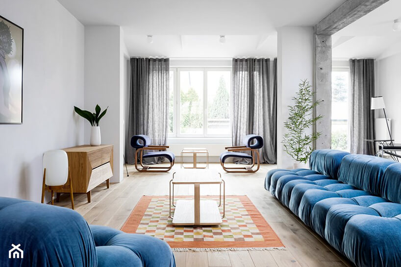 duża niebieska sofa zniebieskim fotelem wjasnym eleganckim salonie