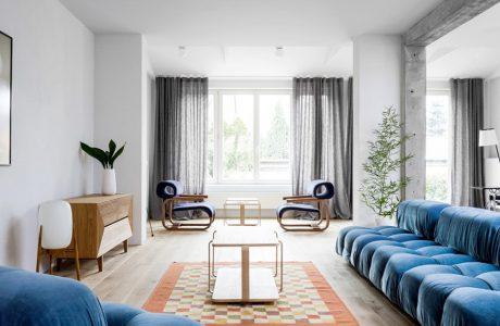 duża niebieska sofa z niebieskim fotelem w jasnym eleganckim salonie