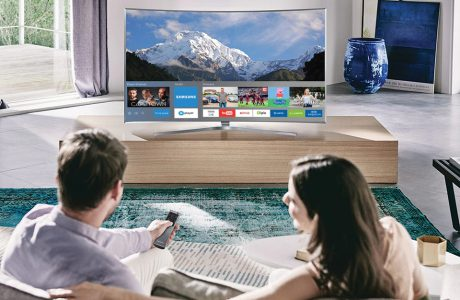 para siedząca na sofie przed dużym telewizorem Samsung z funkcją Smart TV