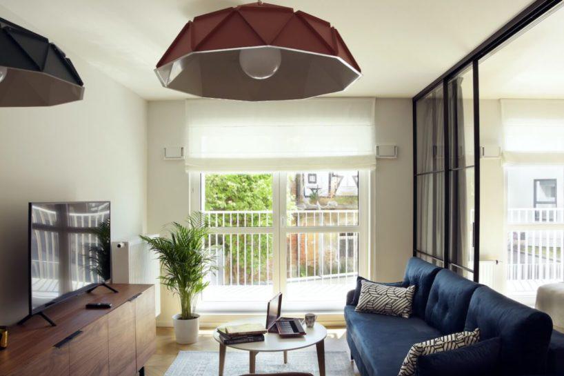 pokój dzienny wkawalerce zgranatową kanapą istolikiem