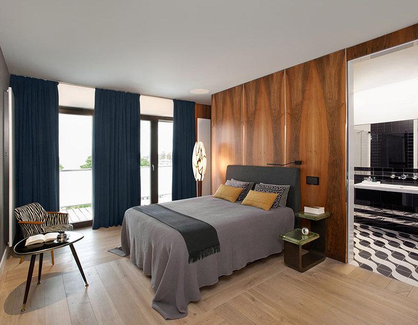duże łóżko wsypialni pod brązową ścianą