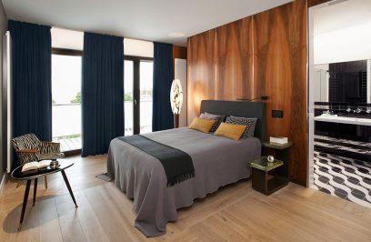 duże łóżko w sypialni pod brązową ścianą