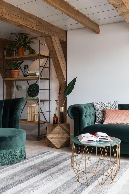 regał otwarty Dutchbone od Dutchhouse wsalonie zodsłoniętymi belkami stropowymi obok zielonej sofy ifotela