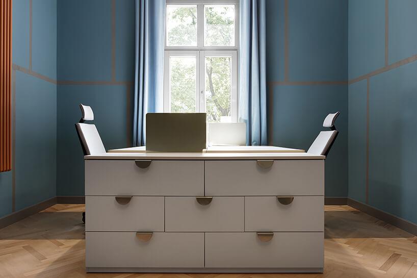 dwa biurka zfotelami ibiałą szafką wniebieskim pokoju