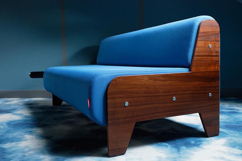 niebieska sofa zciemno brązowym drewnianym stelarzem