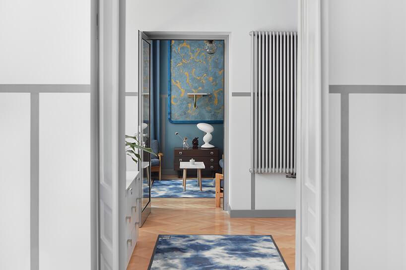widok przez kilka drzwi na pomieszczenia wszarym iniebieskim stylu
