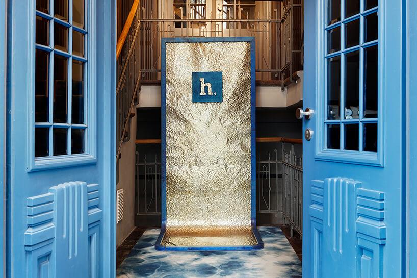 ręcznie formowana blacha wzłotym kolorze za niebieskimi drzwiami