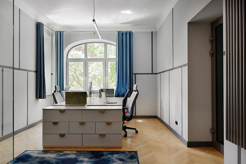 szare pomieszczenie biurowe zniebieskimi zasłonami woknie