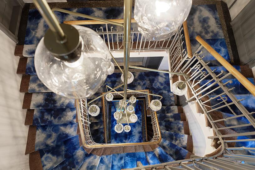 jeden żyrandol wiszący na klatce pomiędzy piętrami