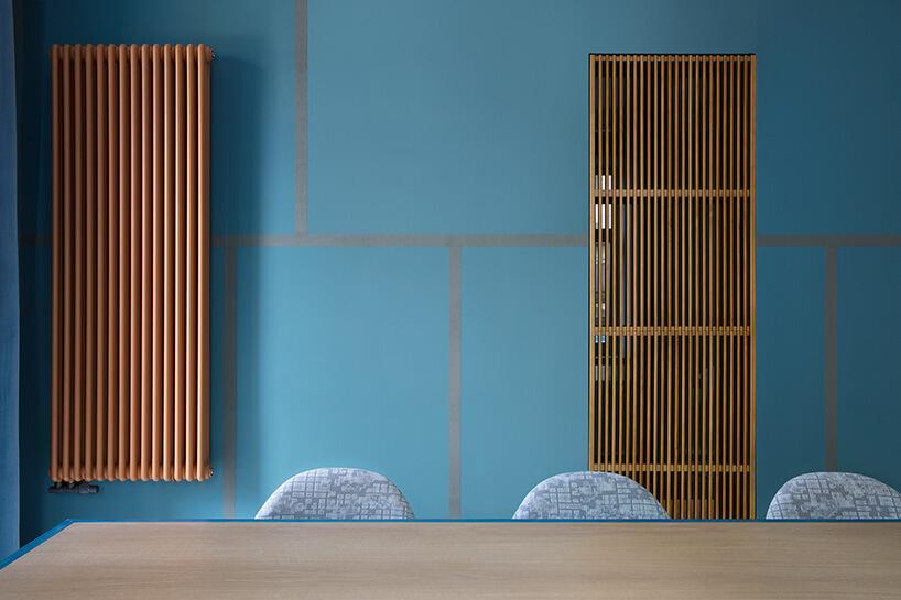 niebieskie pomieszczenie konferencyjne zdużym beżowym grzejnikiem