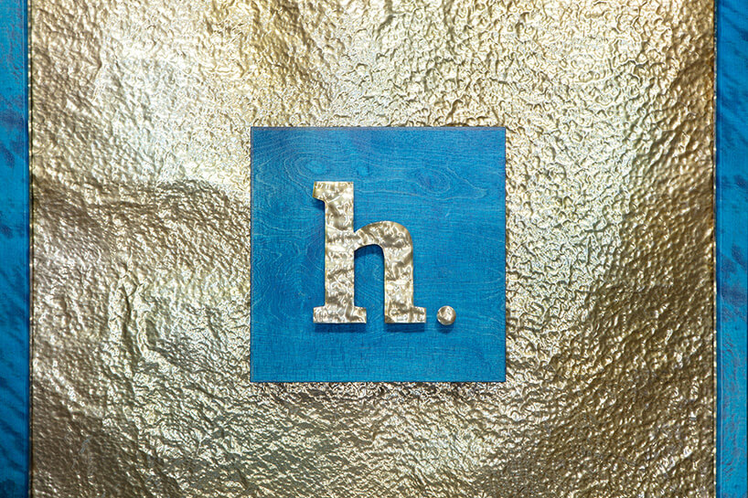 złota litera hna niebieskim tle na młotkowanej złotej blasze