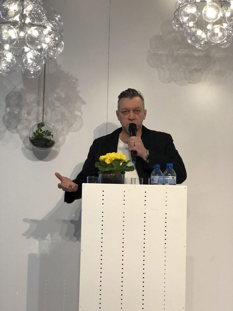mężczyzna zmikrofonem przy mównicy