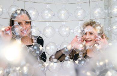 dwie kobiety stojące za nietypowym oświetleniem