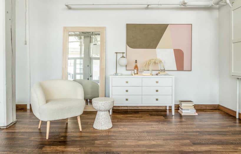 duże jasne wnętrze zjasnymi meblami oraz beżowym fotelem na drewnianych nogach