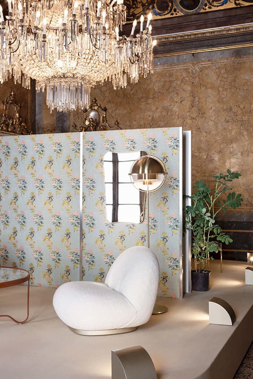 wzorzysta tapeta zzłotym dużym żyrandolem oraz białym niskim fotelem