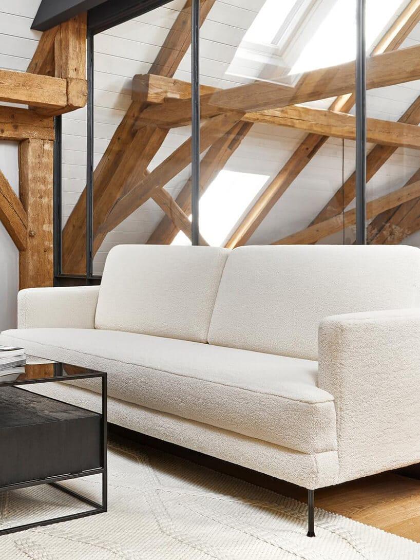 sofa przy szklanej ścianie na poddaszu zdrewnianą konstrukcją