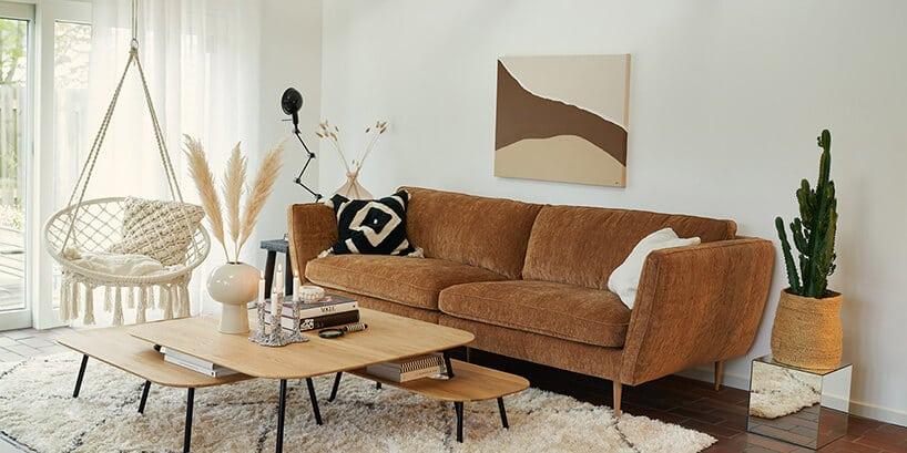 ciemno brązowa kanapa szeroka obok białej wiszącej huśtawki
