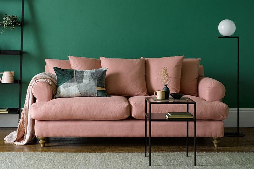 pudrowo różowa kanapa zpoduszkami na tle zielonej ściany
