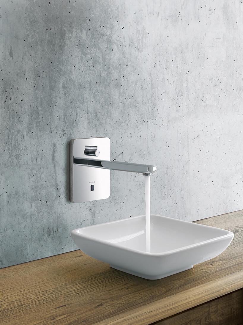 betonowa ściana zchromowanym kranem iprostokątną umywalką