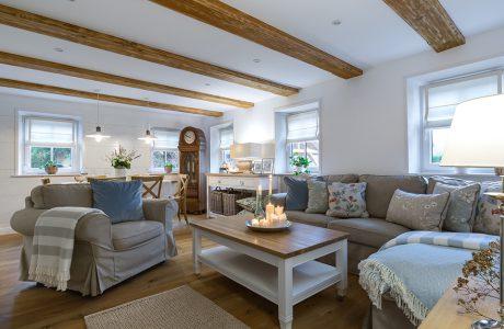 eleganckie klasyczne białe wnętrze salonu z drewnianą podłogą z szarym fotelem i sofą
