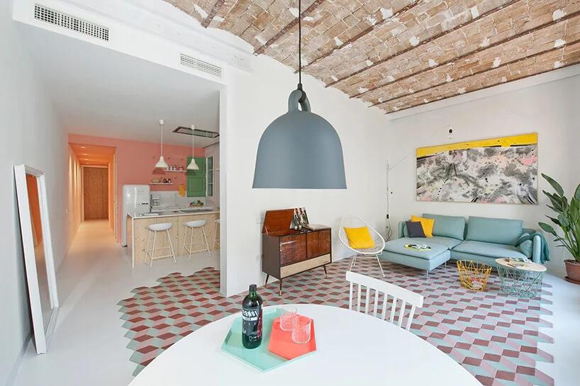 biały salon zjadalnią zzieloną sofą pod kafelkowym sufitem
