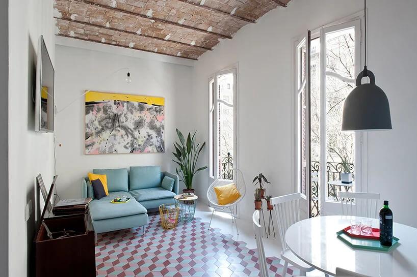 mały biały salon zzieloną sofą obok dużych białych okien