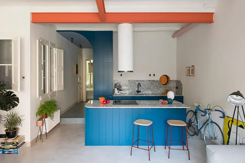 białe wnętrze zaneksem kuchennym zniebieskim akcentem nad wejściem zwyspą zniebieskim wykończeniem ijasnym kamiennym blacie