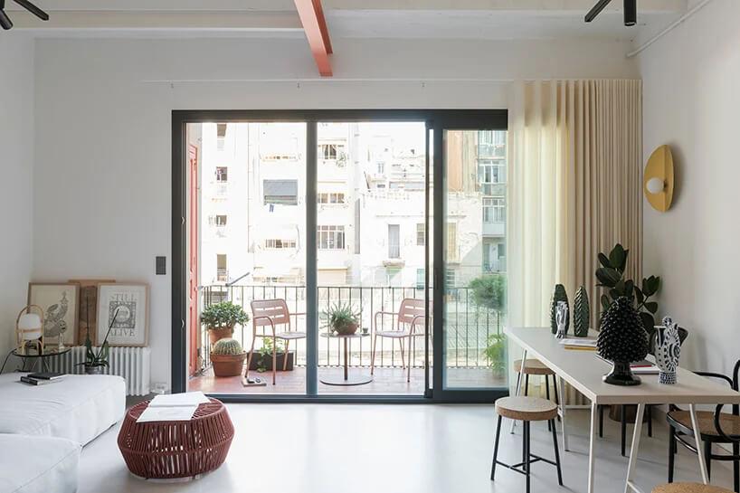 biały salon zdużym drewnianym stołem na tle szarego panoramicznego okna na duży balkon