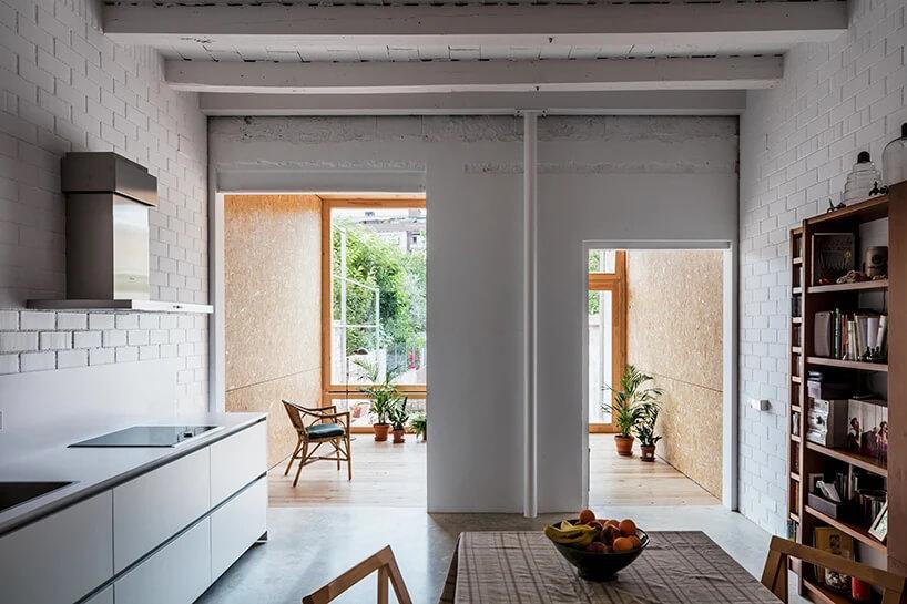 białe wnętrze kuchni zjadalnią zdużym drewnianym stołem zdrewnianą szafką