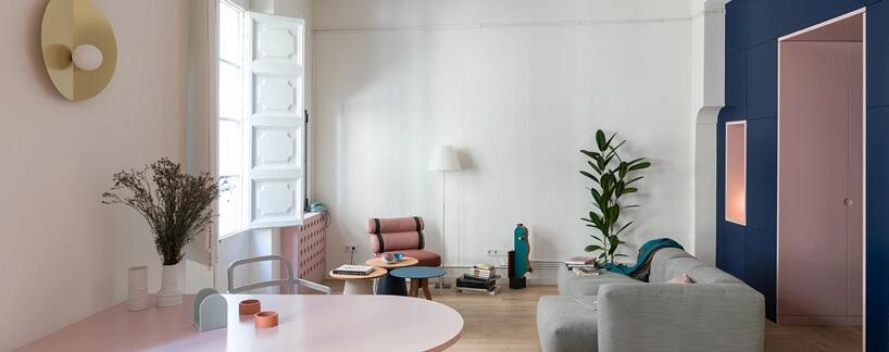 biały salon zdrewnianą podłogą ibiałymi drewnianymi żaluzjami