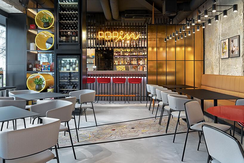 wnętrze restauracji POP in projektu Sikora Wnętrza czarne stoliki zszarymi krzesłami na tle baru zneonem POPin