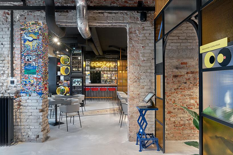 wnętrze restauracji POP in projektu Sikora Wnętrza ceglane ściany zwmontowanymi klockami LEGO wjeden zfilarów