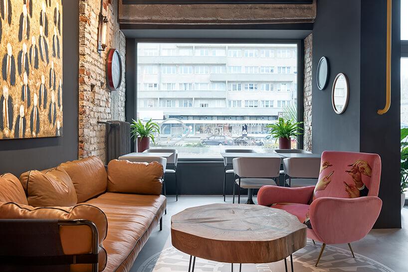 wnętrze restauracji POP in projektu Sikora Wnętrza duża brązowa sofa przy drewnianym stoliku zdrewnianego plastra drzewa